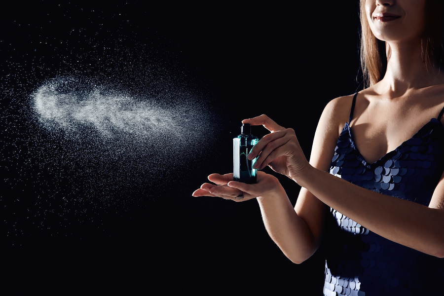 women spraying pheromone bottle