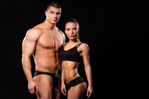 Competitive body building couple standing together